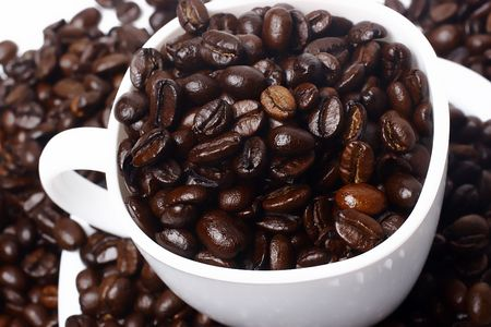 caffiene: cup full of coffee beans closeup