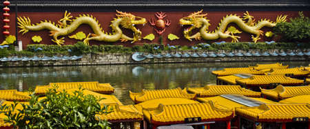 Decorative Golden Dragons on the Wall above a river in Nanjing, China Stock Photo