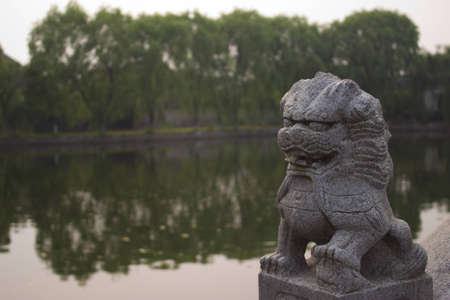 Chinese Lion Statue in Front of a Pond