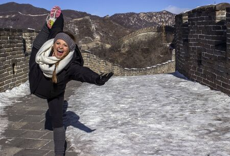 A Female Tourist Practicing Yoga on the Great Wall of China Stock Photo