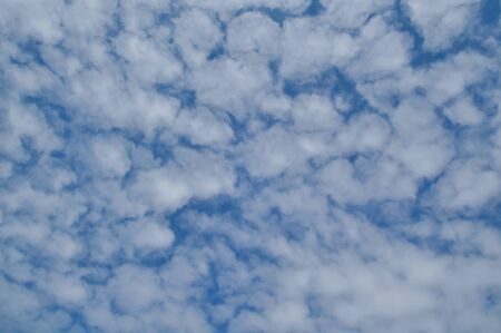Scattered white clouds fill the sky Stock Photo