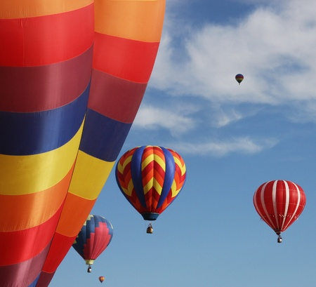 Hot air balloons rising in blue sky