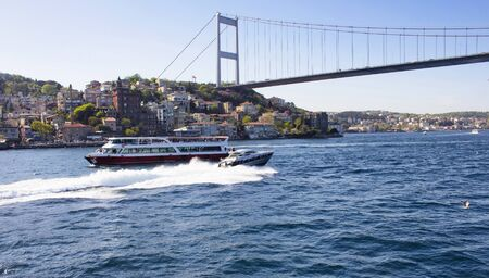 hisari: Cruise boat and luxury boat passes each other under Fatih Sultan Mehmet Bridge