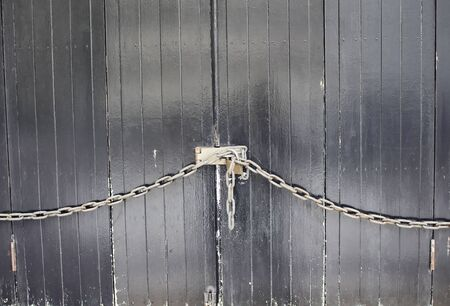 rustiness: Old wooden door chained and locked