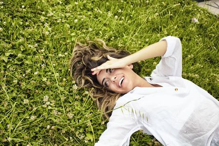 lays down: Beautiful, young, European woman lays down on grass in nature Stock Photo