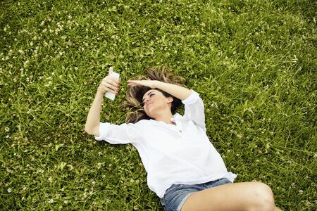 lays down: Beautiful, young, European woman lays down on grass and checks her phone in nature