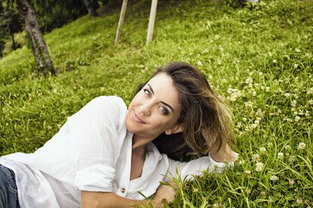 lays down: Beautiful, young, European woman lays down on grass and looks at at camera in nature