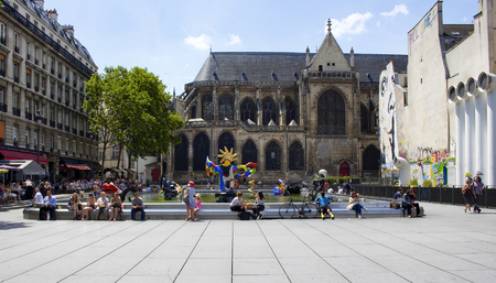sit around: PARIS - JULY, 2016: People sit around Stravinsky fountain and enjoy sunny day in Paris. There are many contemporary artworks in the pool. Editorial