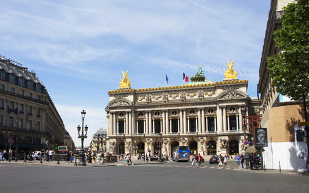 cross street: PARIS - JULY, 2016: Famous opera house in Paris. People cross street and vehicles are in the view.