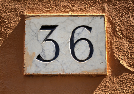 number 36: Engraved building number (36) made with marble on plastered wall in Rome.