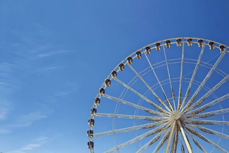 wholeness: Half view of ferris wheel with blue sky background at Jardin Des Tuileries in Paris.