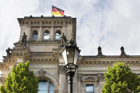glass topped: Bottom view of old, historical street lamp in front of Reichstag building. Neo-Renaissance parliament house topped by a Norman Foster glass dome. German flag waves on top of it.