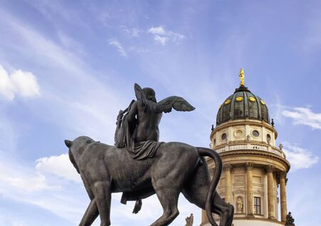 Bottom view of statue of musician angel plays an instrument on lion in Berlin. French cathedral dating back to the 17th century and blue sky are in the background. Stock Photo