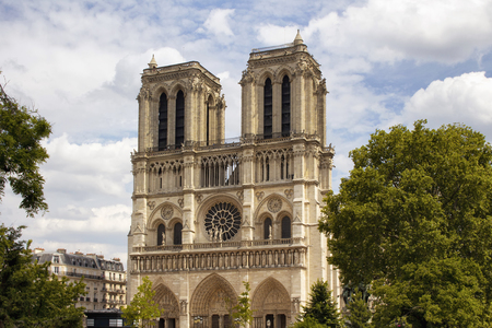 View of Notre Dame Cathedral with trees and cloudy sky in Paris. Towering, 13th-century cathedral with flying buttresses & gargoyles, setting for Hugos novel.