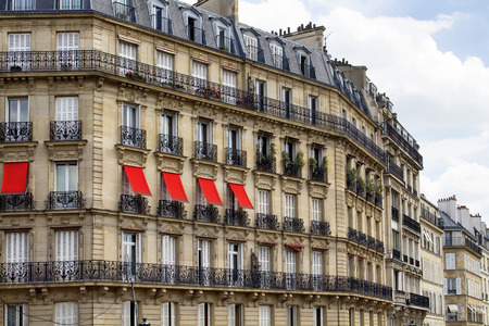 Buildings at 2nd arrondissement in Paris showing 19th century architectural style. Iron, ornamental balconies and plants are in the view. Red sun screensawnings are in the view.