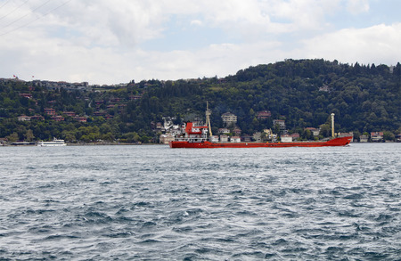 Red, dry cargo ship  vessel crosses Bosphorus strait in Istanbul. Asian side and residential buildings are in the background. It is internationally-significant waterway located in northwestern Turkey