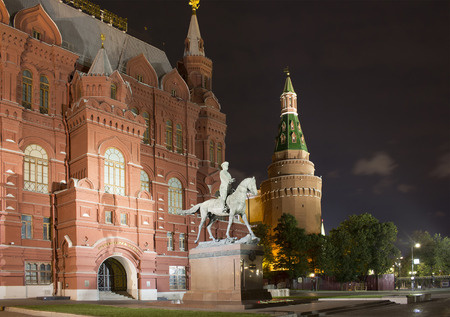 Statue of Marshall Georgy Zhukov in front of State Historical Museum in Moscow at night. Imposing neo-Russian building of 1881, displaying prehistoric relics, Romanov dynasty art & more.