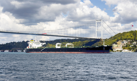 mehmet: Big, dry cargo ship  vessel crosses Bosphorus strait in Istanbul. Asian side and FSM (Fatih Sultan Mehmet) bridge are in the background. It is significant waterway located in northwestern Turkey Stock Photo