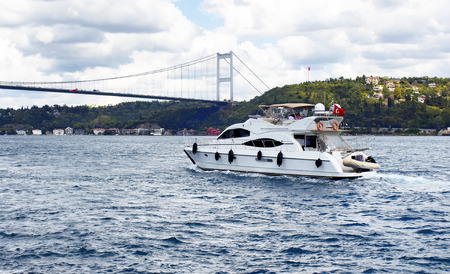 White luxury yacht  boat crosses Bosphorus between European and Asian sides in Istanbul. It is cloudy autumn day. FSM (Fatih Sultan Mehmet) bridge is in the background. Stock Photo