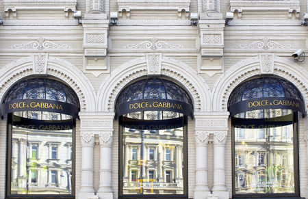 Famous fashion brands stores windows with signage in Moscow city center. Ornamental, historical building showing architectural details.
