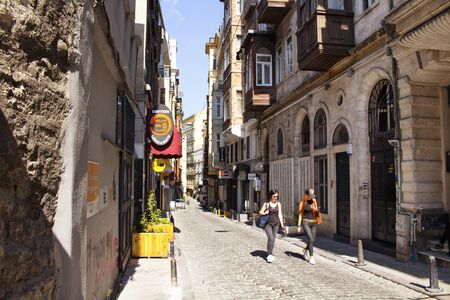 Two women walk on Serdar-i Ekrem street in Galata area of Beyoglu district in Istanbul on a sunny day. Its famous for design shops  stores, cafes. Editorial