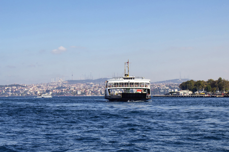 View of car ferry leaving from Sirkeci station. Asian side of Istanbul is in the background. Its a sunny summer day.