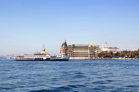 Traditional public ferry passes by historical train terminal named Haydarpasa. Until 2012 the station was a major intercity, regional and commuter rail hub in Turkey. Stock Photo