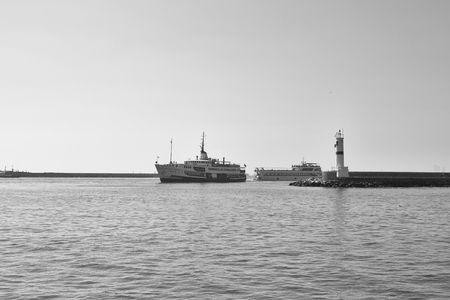 blackwhite: Black and white photography of traditional public ferry arriving to Kadikoy station. Water breaker and a motorboat are also in the view. Stock Photo