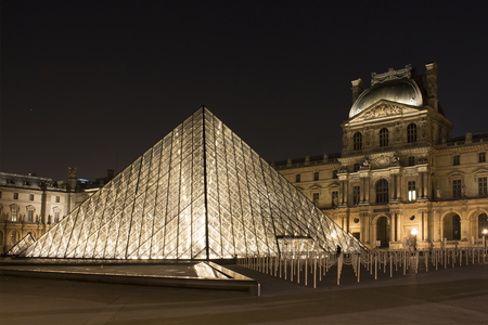 Night view of glass pyramid at Louvre Museum (Musée du Louvre). Former historic palace housing huge art collection, from Roman sculptures to da Vincis Mona Lisa.