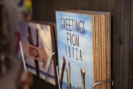 Close up view of souvenir on rack saying Greetings from Ibiza. Photography and text illustrations are printed on wood.