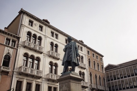 View of Daniele Manin statue from the 1875 monument by Luigi Borro in Venice.  Old, historical building are in the background with sunlight in early in the morning.
