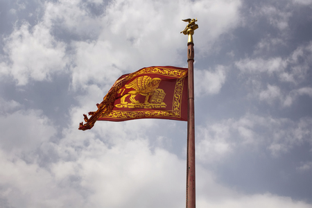 View of historical Venetian flag waving with cloudy sky background.