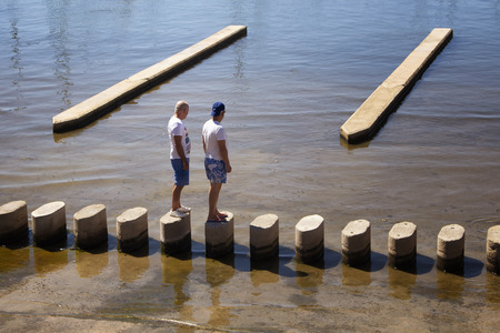 Two men stand and look at sea at Palma de Mallorca marina. It's a resort city and capital of the Spanish island of Majorca in the western Mediterranean.