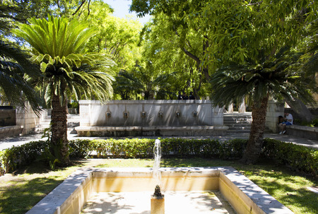 View of water fountain and trees at Hort del Rei park next to Royal Palace of La Almudaina and Catedral de Mallorca