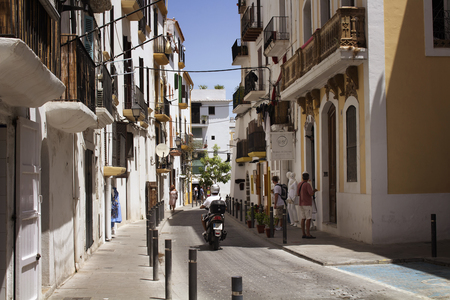 View of a man riding motorcycle and people on one of narrow, historical streets in Ibiza old town. Image reflects culture and lifestyle of the island.