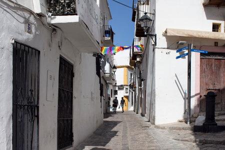 Due turisti di giovani uomini di colore camminano in strada gay di Ibiza durante il giorno. La strada stretta e gli edifici bianchi e tradizionali riflettono lo stile di vita e la cultura dell'isola. È Calle de la Virgen.