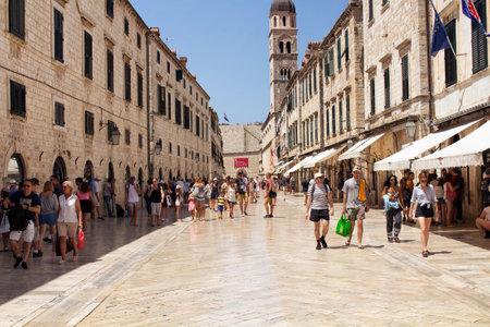 多くの観光客は、晴れた夏の日にドゥブロヴニク旧市街の主要な通り(ストラドゥン)の一つを歩きます。