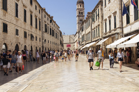 Many tourists walk on one of the major streets (Stradun) in Dubrovnik old town on sunny summer day. 新闻类图片