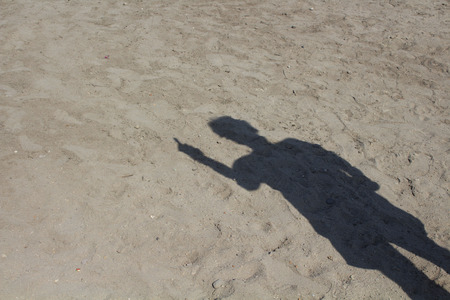 Shadow of man doing an obscene hand gesture on sand background.