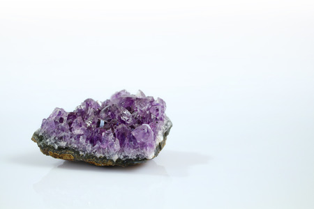 Isolated precious amethyst gemstone with white background. It's is a violet / purple variety of quartz often used in jewelry. 写真素材