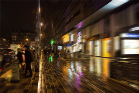 Blurry motion image of people walking on street at night in Paris. Stock Photo