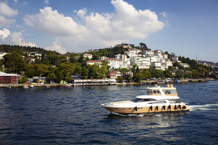 View of unrecognizable people riding a luxury yacht on Bosphorus. Houses on Asian side of Istanbul are in the background. It is a sunny summer day. Фото со стока