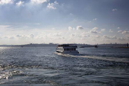 View of public ferry boat, Bosphorus strait and European side of Istanbul in a sunny summer day.