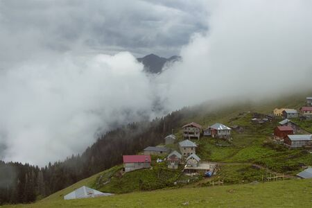 View of a mountain (high plateau) village named Gito, forest trees, glass field and fog. The image is captured in Rize area of Black Sea region located at northeast of Turkey.