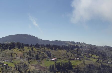 View of high plateau village, forest and mountain in fog creating beautiful nature scene. The image is captured in Trabzon/Rize area of Black Sea region located at northeast of Turkey.