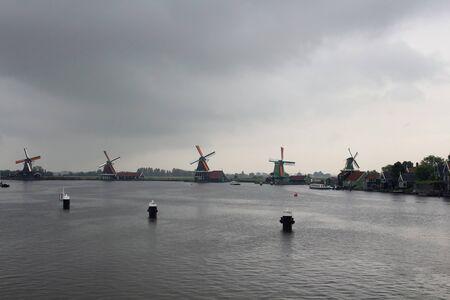 View of windmills in Zaanse Schans, neighborhood in the Dutch town of Zaandam, near Amsterdam. It is a rainy summer day. Stock fotó