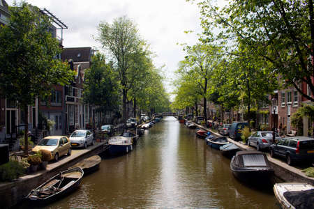 View of canal, trees, parked cars, historical and traditional buildings showing Dutch architectural style in Amsterdam. It is a sunny summer day. Stock fotó