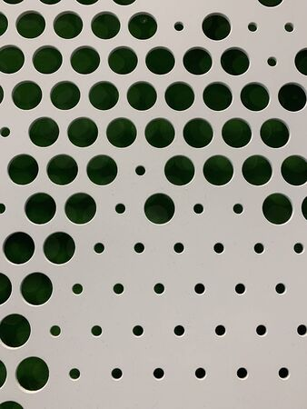 Close up view of white metal surface with green color background. Dotted graphic pattern is cut out.