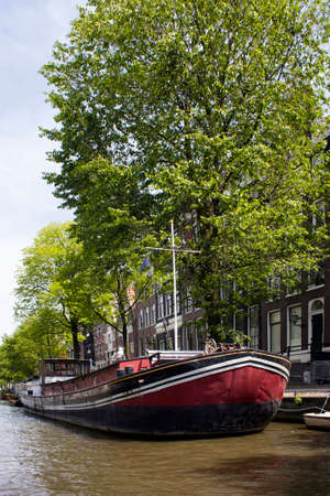 View of canal, boat house, trees and historical, traditional buildings showing Dutch architectural style in Amsterdam. It is a sunny summer day.