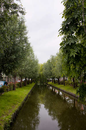 View of a river and trees in Voldendam. It is a Dutch town, northeast of Amsterdam. It's known for its colorful wooden houses and the old fishing boats.
